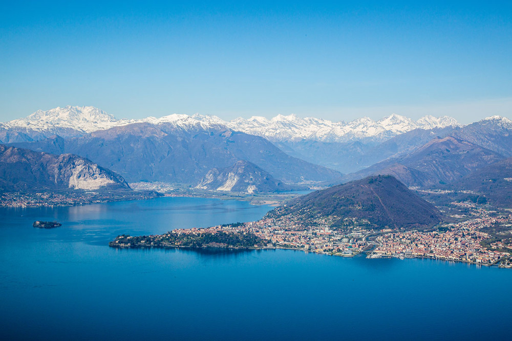 At Laveno, Lake Maggiore a cable car climbs from lake level (at 190m) to Mount Sasso del Ferro (at 1,100m). Noteworthy in the picture: Pallanza on the very tip of the peninsula; the massif of Monte Rosa, the second highest peak in Europe (at 4,634m).